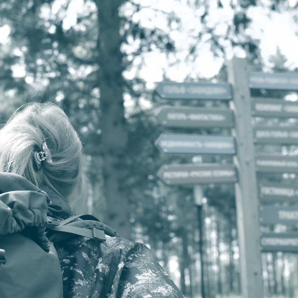 Photo of the back of a woman's head looking at signposts in a wooded trail. Showing how our employee benefits company helps you to build.