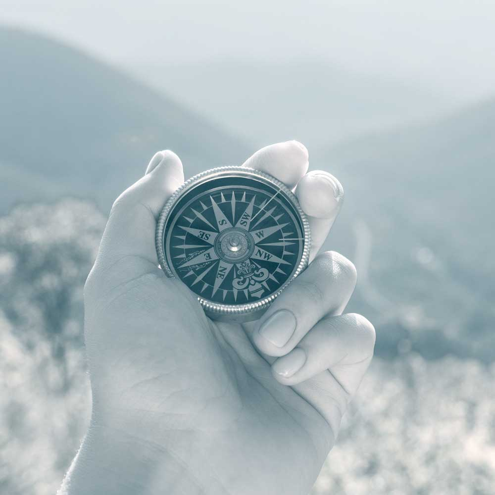 Photo of a hand holding a compass in the mountains, showing how a good employee benefits company can help you find the way.